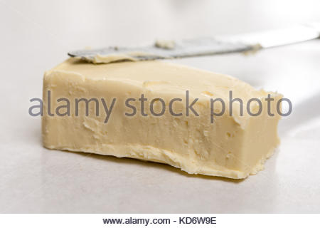 Slice of butter with kitchen knife on the white marble background table. - Stock Image