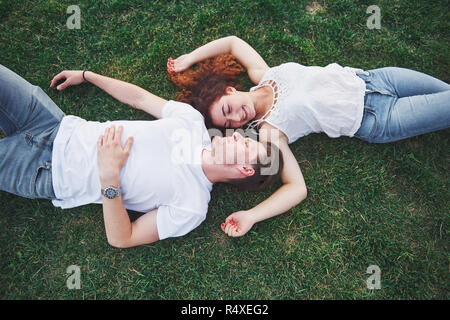 Cheerful couple lying on the grass. Young people outdoors. Happiness and harmony. - Stock Image