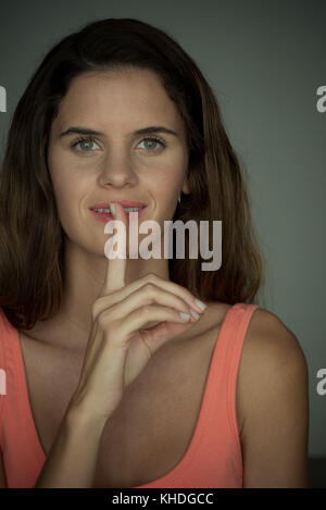 Young woman smiling with finger held to lips - Stock Image