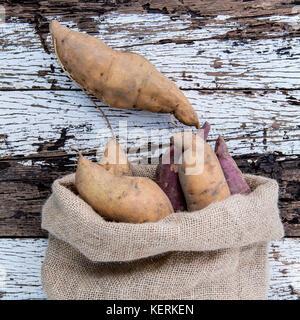 Harvested organic sweet potatoes in a hemp sack bag on rustic wood table. - Stock Image