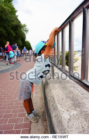 Kolobrzeg, Poland - August 10, 2018: Young boy with shorts and hat holding on a barrier. It is build along the promenade with view to the beach. The c - Stock Image
