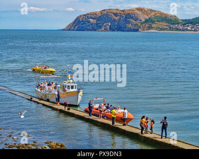 25 July 2018: Llandudno; Conwy; UK - People on the boardwalk or jetty; getting on and off the Sea Jay and a Jet Boat; for rides around the bay, with.. - Stock Image