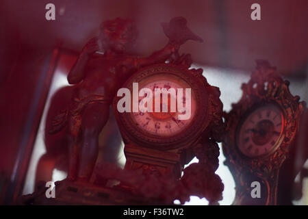 antique clock with red hue cast over - Stock Image