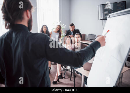 Portrait of a happy creative team of people talking in the office at the meeting. - Stock Image