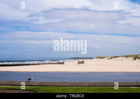 View to east beach and sand dunes across Lossie River mouth from waterfront promenade on Moray Firth coast. Lossiemouth, Moray, Scotland, UK, Britain - Stock Image