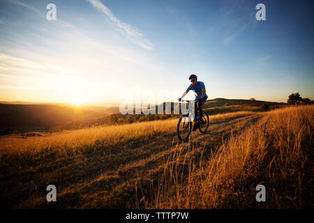 Man cycling on field against sky during sunset - Stock Image
