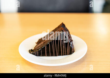 A slice of chocolate cake with icing served on a white plate on an office desk, UK. - Stock Image