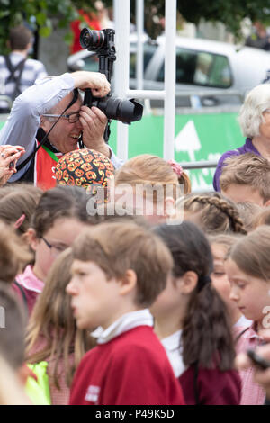 Photographer working at the 2018 OVO Women's Tour with a crowd of school children in the forground - Stock Image