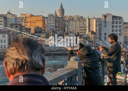 Anglers on Galata bridge. Galata tower can be seen dominating the Beyo?lu skyline in the background. - Stock Image