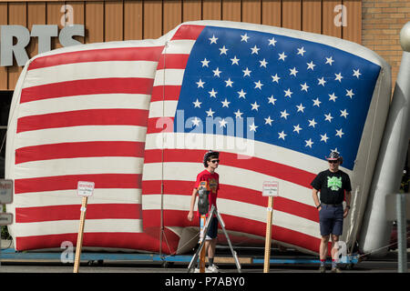 Anchorage, Alaska. 4th July, 2018. A giant inflatable flag is marched down the street during the annual Independence Day parade July 4, 2018 in Anchorage, Alaska. Credit: Planetpix/Alamy Live News - Stock Image