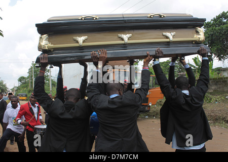 Pall bearers performing the final burial rites at a village in Nigeria. - Stock Image