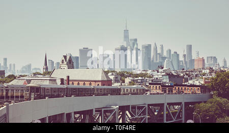 Retro toned picture of a subway train with New York City skyline, USA. - Stock Image