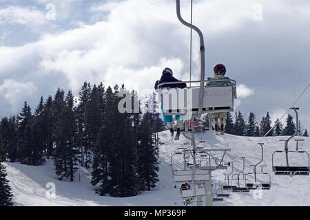 A couple have a ride with a chairlift. - Stock Image