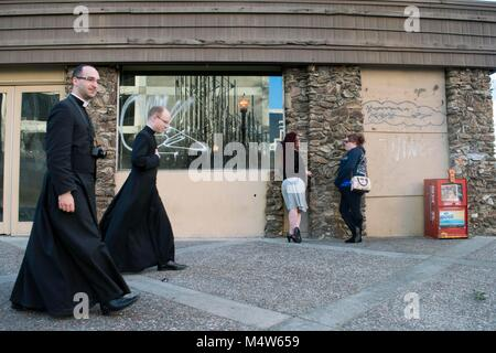 Two women chat in Sacramento while priests walk down the street. - Stock Image