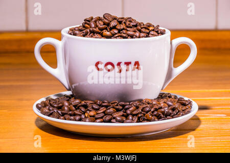 Costa coffee: logo on extra large cup (with dual handles), sitting on saucer, full of roasted whole coffee beans, - Stock Image