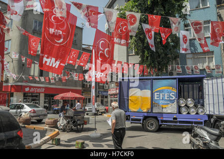 A beer delivery truck on a street lined with MHP (a far-right nationalist political party) electoral flags, in Istanbul. - Stock Image