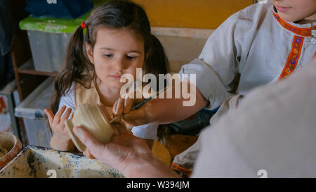 Potter showing how to work with ceramic in pottery studio - Stock Image