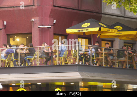 Patrons enjoy their meals at a local Mexican restaurant named Guzman y Gomez in Adelaide, South Australia, Australia. - Stock Image