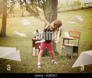 A little child is pretending to be a pilot flying paper airplanes in a classroom outside for a education or creativity - Stock Image