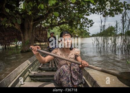 A woman paddles through stilt villages in the flooded Irrawaddy delta, Myanmar. - Stock Image