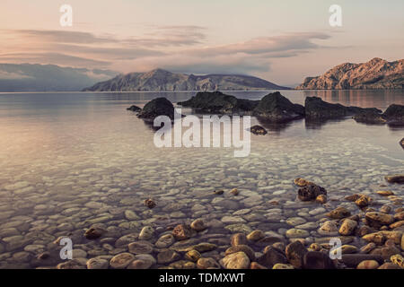 Amazing beach sunset with mountain in the distance, and stars over the sky in Croatia - Stock Image