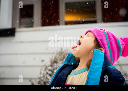 Four-year old girl catches snow on her tongue during a winter storm in the United States in November. - Stock Image