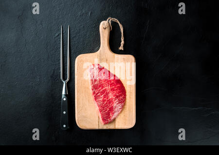 Kobe meat, wagyu beef steak, raw, shot from the top with a carving fork on a black background with a place for text - Stock Image