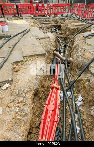 Underground electrical services and cables in trench exposed during utility services upgrade in Oakham town centre, Rutland, England, UK - Stock Image