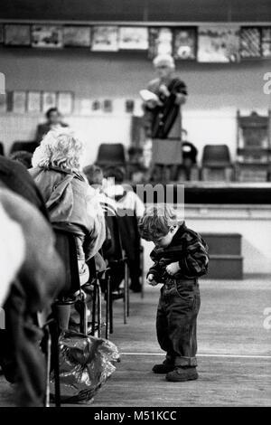 Boy adjusting belt in audience at small eisteddfod in village hall Trawsfynydd Gwynedd Wales UK - Stock Image
