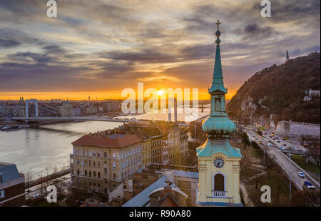 Budapest, Hungary - Church tower and Elisabeth Bridge with a beautiful sunrise over Budapest - Stock Image