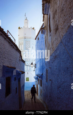 Chefchaouen, Morocco : A man walks in a blue-washed alleyway under the minaret of a mosque in the medina. - Stock Image