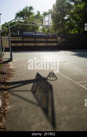 Solitary Basketball Hoop On Light Blue Asphalt Court In School Playground - Stock Image
