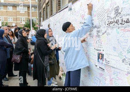 London, UK. 15th June, 2017. A man writes a message of condolence to the victims of the Grenfell Tower fire. The - Stock Image