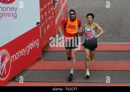 London, UK, 28 April 2019 Yap Tien-Fung of Germany. Runners at finishing line of  Virgin London Marathon Credit: JOHNNY ARMSTEAD/Alamy Live News - Stock Image