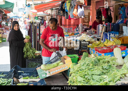 Muslim woman customer at the famous Ballero street market for vegetables and other fresh food in Palermo, Sicily, Italy - Stock Image