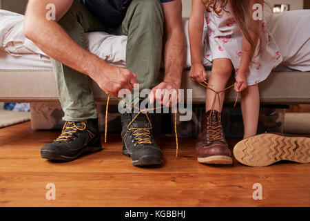 Dad teaching his daughter how to tie shoelaces, low section - Stock Image