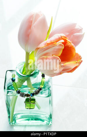 Cut tulips in a decorative glass vase with a pendant - Stock Image