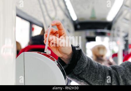 bus ticket insert validator  hand background - Stock Image