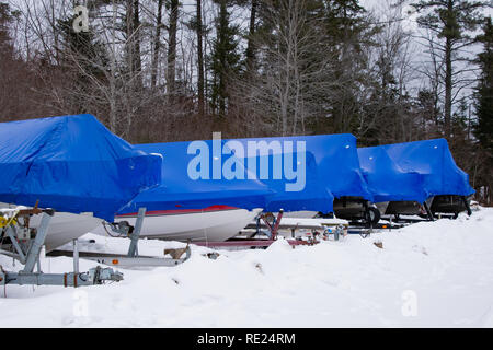 A row of boats sitting on trailers in the snow covered with blue polymer plastic film shrink wrap for protection in Speculator, NY USA - Stock Image