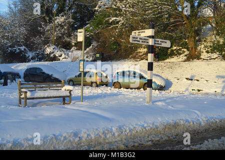 Grass triangle in the north Oxfordshire village of Hook Norton in the aftermath of a severe snowfall - Stock Image
