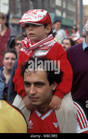 Arsenal fans Father and son after football game wearing the the team colours - Stock Image