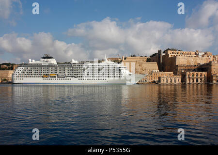 The residential cruise ship The World beneath the walls of Valletta in Malta's Grand Harbour. Travel and tourism in the Mediterranean Sea. - Stock Image
