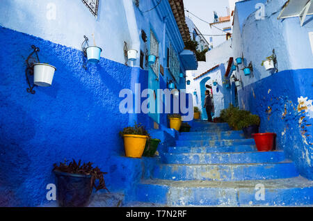 Chefchaouen, Morocco : Flowerpots at a steep blue-washed alley in the medina old town. - Stock Image