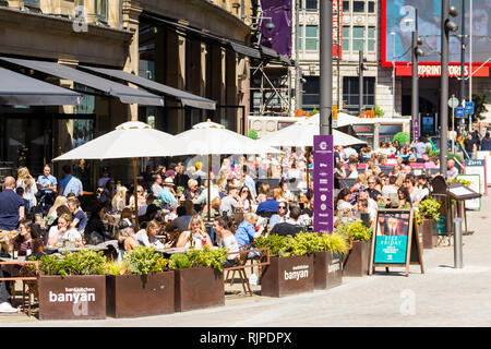 A summer day in Manchester city centre with many people sat eating and drinking outside Banyan Bar and other restaurants and bars of The Triangle, for - Stock Image