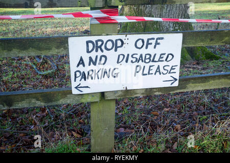 Hand-written sign pinned to a wooden fence in the countryside 'Drop off and disabled parking please'. - Stock Image