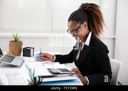 Side View Of Young Businesswoman Calculating Invoice On Computer Screen Near Laptop - Stock Image