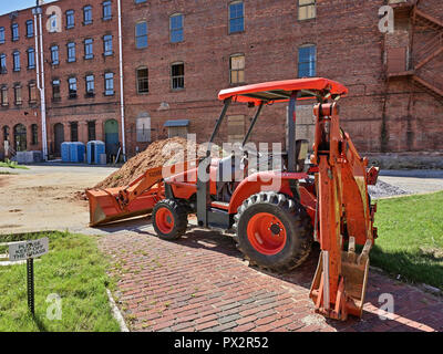 Orange Kubota HST tractor front loader with backhoe attachment on a construction site in Montgomery, Alabama, USA. - Stock Image