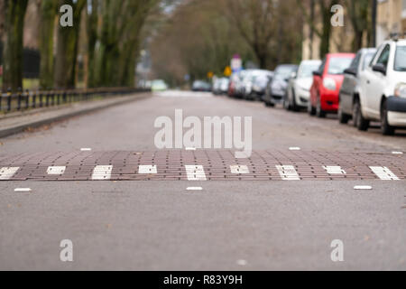 speed bump on empty street in Warsaw, Poland, cars on one side of the street, challenge symbol - Stock Image