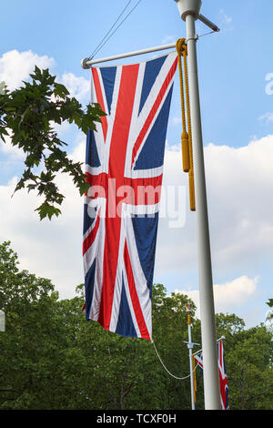 Union Jack flag flying from a roadside flagpole in The Mall, London, UK in spring with green trees and blue sky - Stock Image
