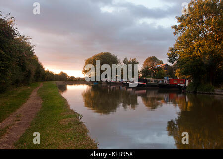 narrowboats and towpath along Cooks Wharf at sunset, Grand Union Canal Outer Aylesbury Ring, Cheddington, Buckinghamshire, - Stock Image